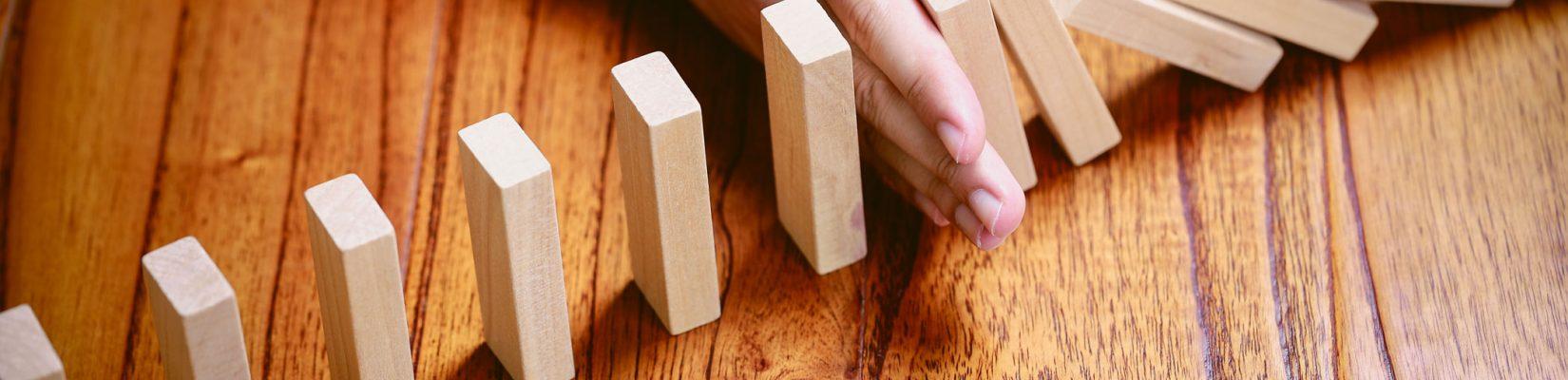Hände halten Dominosteine auf